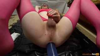 TS-girl in pink stockings is entertained with a transparent dildo